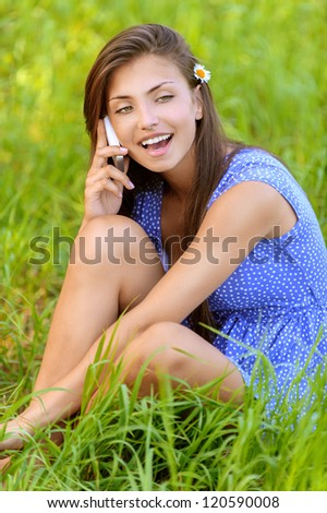 Charming dark-haired happy young woman sitting on grass and talking on cell phone, against background of summer green park.