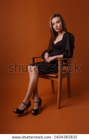 charming elegant fashion model wearing black dress, high heel shoes posing on orange background. asian young woman sits on chair in sexy evening gown. beautiful sensual glamorous girl poses in studio