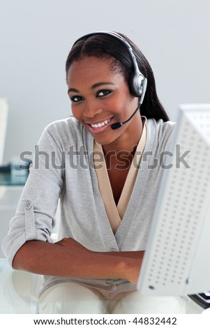 Charming ethnic customer service agent with headset on at her desk