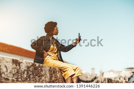 Charming fancy African hipster female is taking a selfie while sitting on a stone wall outdoors; stylish black girl in yellow overalls and a denim jacket is taking pics on her cellphone on the street