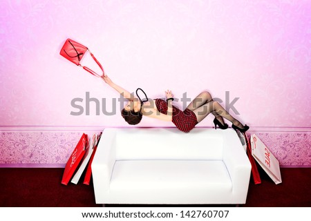 Charming fashionable woman flying over the sofa in the room with her bag. #142760707