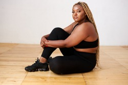 charming fat black female sit relaxing in studio with white background, beautiful woman in black sportswear look at camera, plus size model