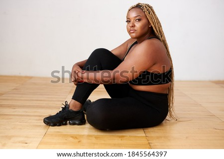 charming fat black female sit relaxing in studio with white background, beautiful woman in black sportswear look at camera, plus size model Foto stock ©