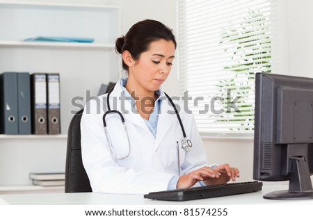 Charming female doctor typing on a keyboard while sitting in her office - stock photo