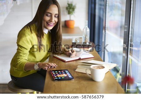 Charming female owner of restaurant business spending free time in cafe waiting for meeting with investors while playing online games on touchpad with mock up screen connected to wireless internet Stock photo ©