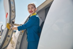 Charming female stewardesses in blue uniform looking at camera and smiling while placing hand on aircraft door