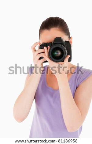 Charming female using a camera while standing against a white background