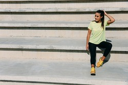 Charming fitness woman wearing yellow t-shirt, black leggings and sport sneakers sitting on stairs and enjoying sunbeams. Young lady spending free time for training on fresh air.