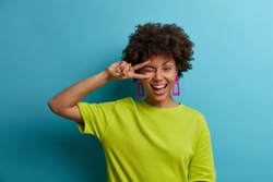 Charming friendly African American woman makes peace sign over eye, smiles broadly and feels positive emotions, sends good vibes, wears bright green t shirt. People, emotions, summertime concept