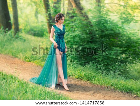 charming gentle angel descended from sky and cautiously walks along forest path. cute princess in long elegant elegant expensive dress with dark braided hair decorated with flowers, sexy bare legs