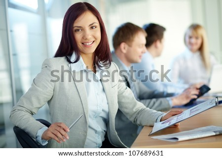 Charming girl holding a folder and looking at camera with a smile