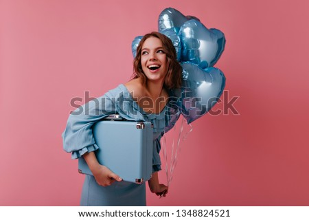 Charming girl in blue dress posing with balloons and valise. Studio shot of happy white lady having fun at party after travel.