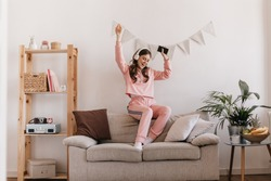 Charming girl in tracksuit dancing, sitting on couch. Woman holding smartphone and listening to music with headphones. Shot of teen in pink home suit having fun in cozy home atmosphere