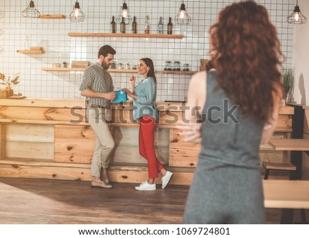 Charming girl is flirting with man and smiling. She is touching gift present in male hands with curiosity. Young woman standing in front of them while feeling jealousy. Adultery concept