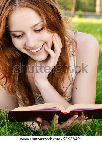 Charming girl reads book on green grass.