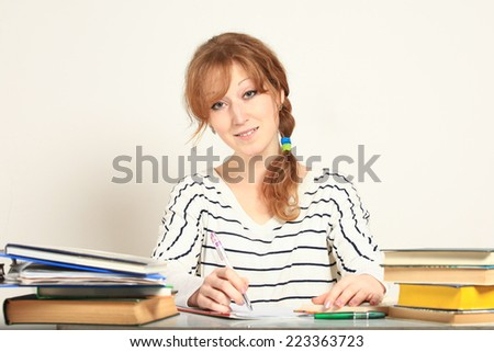 Charming  girl sitting at table with books studying writing in notebook