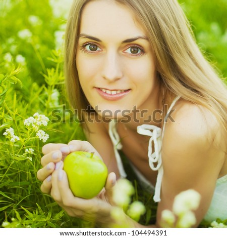 Charming girl with apple lies on green grass