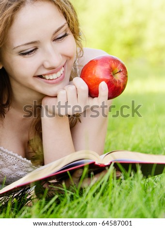 Charming girl with apples lies on green grass and reads book. #64587001