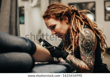 Charming girl with dreadlocks and tattoos stuffs a tattoo on a woman's leg in a tattoo parlor, creative small business and tattoo master. Hipster woman in gloves draws a tattoo