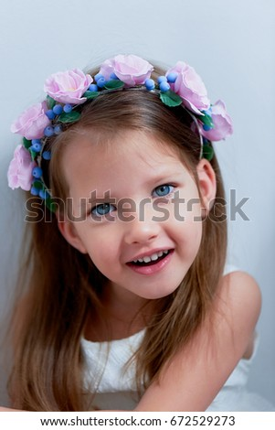 Charming girl with long ash-blond hair , lively blue eyes and a pinched nose, the bezel is handmade . Smiling, holding your hands up.Smiling and looking at camera