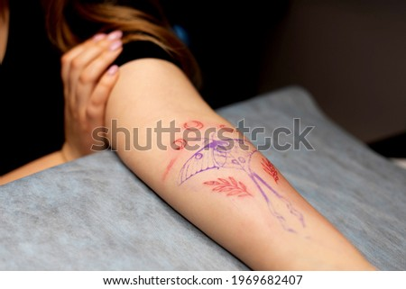 Charming girl with pink hair and tattoos stuffs a tattoo on a woman's hand in a tattoo parlor, creative small business and tattoo master. Hipster woman in gloves draws a tattoo