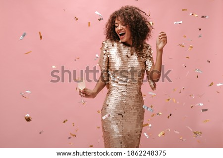 Charming girl with wavy short hair in shiny beige dress holding glass with champagne and posing with confetti on pink backdrop..