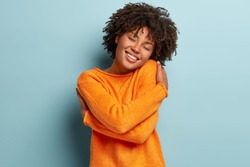 Charming gorgeous Afro woman keeps eyes closed, smiles with pleasure, shows white teeth feels comfort, hugs herself, wears orange jumper, tilts head, models over blue background, has high self esteem