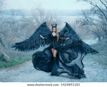 charming gorgeous dark goddess controls wind, air flow waves hem and long train of light black dress with wide lace sleeves, lady with sharp horns and black feather wings ready to fly into sky #1424891183