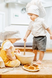 Charming grimy caucasian children cook dough and pancakes while sitting on a table in the kitchen at the weekend. The concept of restless children of researchers. Homework for Preschool Children