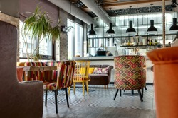 Charming hall in a loft style in a mexican restaurant with open kitchen on the background. In front of the kitchen there are wooden tables with multi-colored chairs and sofas. On the sofas there are
