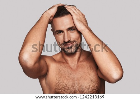 Charming handsome. Charming young man keeping hands in hair and smiling while standing against grey background