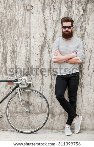 Charming handsome. Full length of young bearded man keeping arms crossed and looking at camera while standing near his bicycle against the concrete wall #311399756