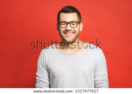 Charming handsome. Handsome cheerful young man in casual wear smiling while standing isolated on red background. #1317477617