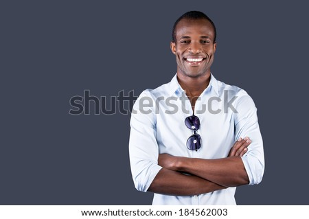 Charming handsome. Handsome young black man in blue shirt keeping arms crossed and smiling at camera while standing against grey background