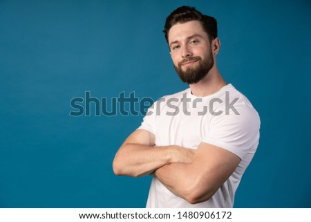 Charming handsome. Handsome young man in casual wear keeping arms crossed and smiling while standing isolated on blue background. Add space. #1480906172