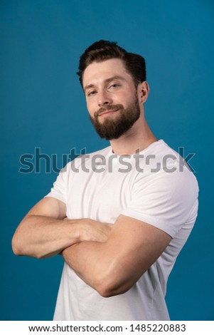 Charming handsome. Handsome young man in casual wear keeping arms crossed and smiling while standing isolated on blue background. Vertical photo. #1485220883