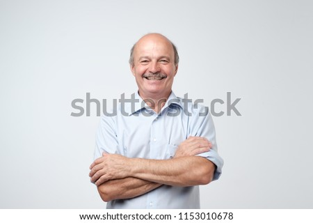 Charming handsome senior man in casual blue shirt keeping arms crossed and smiling while standing isolated on white background.