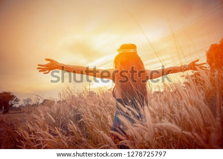 Charming Hippie girl lifestyle. Beautiful carefree woman in fields being happy open hands outdoors on sunset in nature  summer. Beauty girls in Bohemian dress on flower field with ears. Happy dance