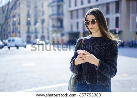 Charming hipster girl in trendy sunglasses and trendy outfit dialing number on phone calling taxi while standing near copy space area for advertising, attractive tourist sending messages strolling #657755380