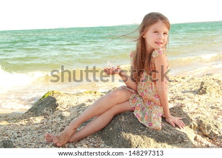 Charming joyful little girl in a summer dress dreaming and smiling at the beach
