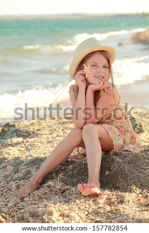 Charming joyful little girl in a summer dress dreaming and smiling at the beach on a summer day/Lovely girl with a beautiful smile playing barefoot in the water on the beach
