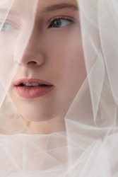 Charming lady in beautiful veil looking away and keeping lips slightly parted
