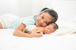 Charming little asian brother and sister in blue shirt asleep embracing on white bed in bedroom. Asia children girl smilie and looking camera sleep with newborn sister. People healthy concept.