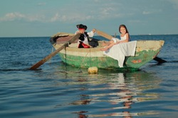 Charming little boy dressed as a pirate and his old lady floating in a boat on a background of blue sea/Theatrical performance of the pirates outdoors