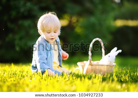 Stock Photo Charming little boy hunting for easter egg in spring park on Easter day. Cute little child with traditional bunny celebrating feast outdoors