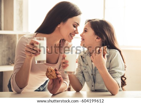 Charming little girl and her beautiful young mom are eating muffins with milk and smiling while resting at home #604199612