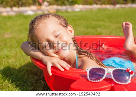 charming little girl enjoying her vacation in the pool outdoors