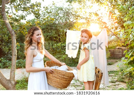 Charming little girl helping mother with wicker basket while doing chore and hanging laundry in backyard in summer evening Photo stock ©