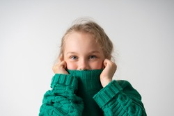 charming little girl hides her lower face under the thick collar of a warm knitted sweater. Children, gestures and emotions, happiness, winter. Close up studio shot isolated on white, copy space
