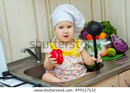 35b791cf867 Charming little girl in a chefs hat sitting in the sink with a ladle in his